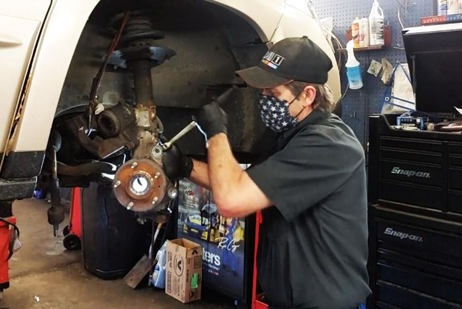 mechanic working on vehicle at berube's auto care garage
