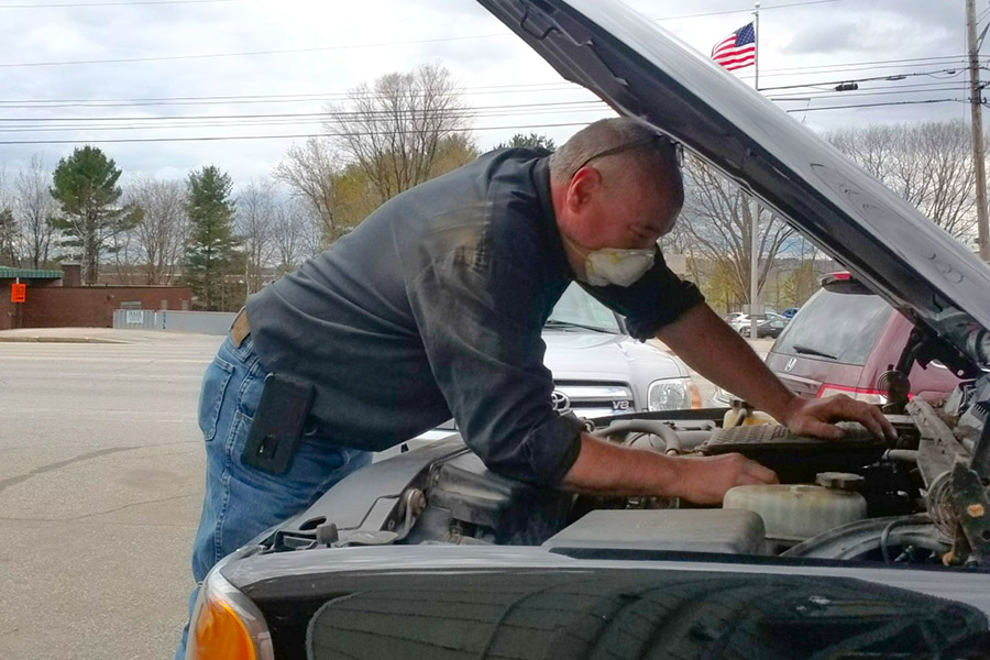 mechanic working under hood of vehicle maine auto repair